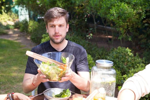 Retrato de hombre joven serio que pasa la ensalada en el almuerzo al aire libre