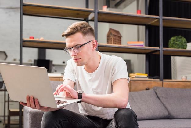 Retrato de un hombre joven serio que se sienta en el sofá usando la computadora portátil