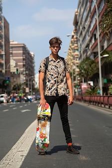 Retrato de hombre joven skater con cara de chico malo en medio de la calle.