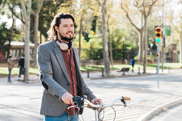 Retrato de un hombre joven sonriente que se coloca con la bicicleta en el camino