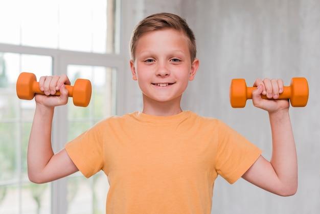 Retrato de un hombre joven sonriente que lleva a cabo pesa de gimnasia en las manos que miran la cámara