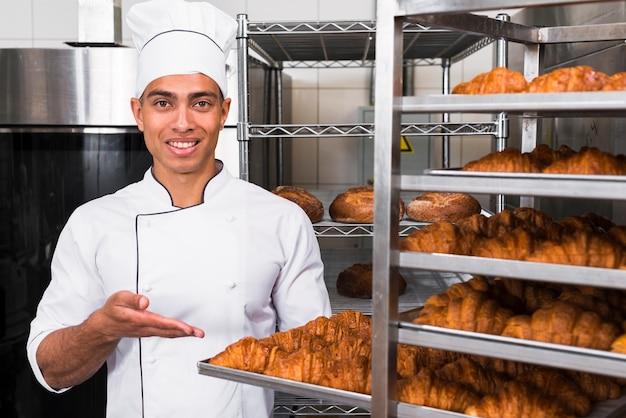 Retrato de un hombre joven sonriente que muestra un croissant recién horneado en la bandeja en el estante