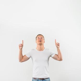 Retrato de un hombre joven sonriente que señala los dedos hacia arriba mirando hacia arriba contra el fondo blanco