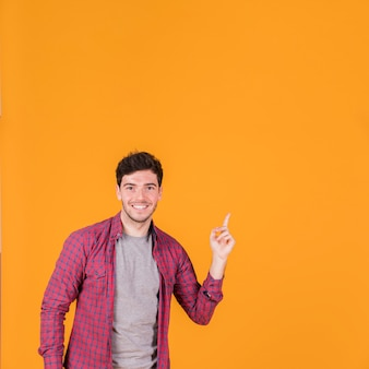Retrato de un hombre joven sonriente que señala su dedo hacia arriba contra un fondo naranja