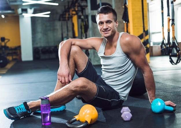 Retrato de un hombre joven sonriente que se sienta en piso cerca de equipos del ejercicio en gimnasio
