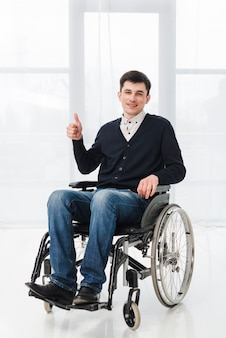 Retrato de un hombre joven sonriente que se sienta en la silla de ruedas que muestra el pulgar encima de la muestra