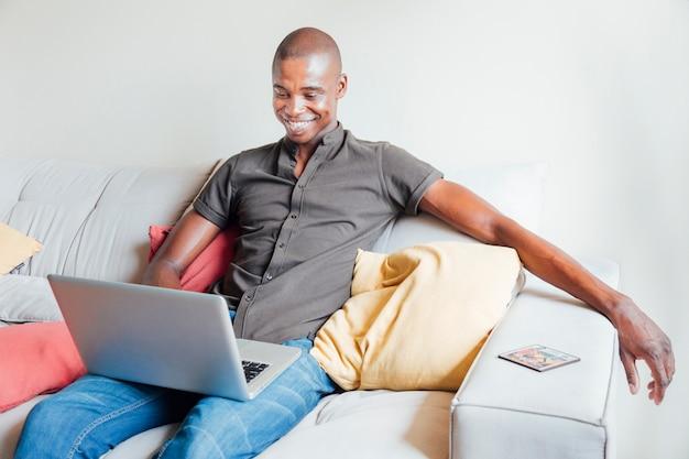Retrato de un hombre joven sonriente que se sienta en el sofá usando la computadora portátil