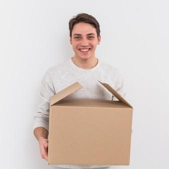 Retrato de un hombre joven sonriente que sostiene la caja de cartón contra el fondo blanco