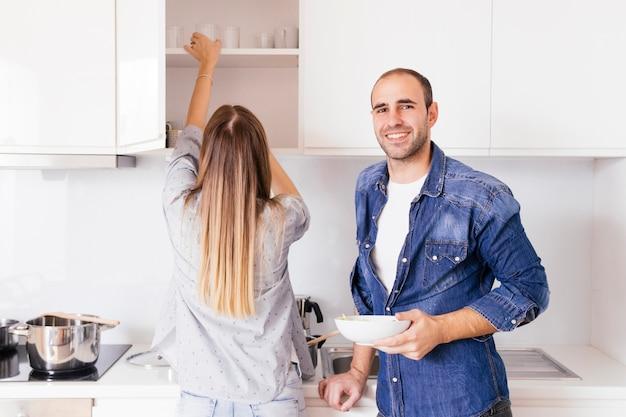 Retrato de un hombre joven sonriente que sostiene el cuenco en las manos que se colocan cerca de su esposa en la cocina