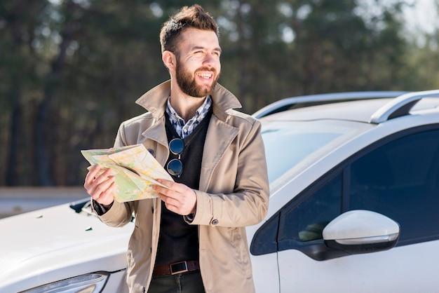 Retrato de un hombre joven sonriente que sostiene el mapa en la mano que se coloca cerca del coche que mira lejos