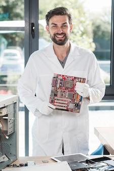 Retrato de un hombre joven sonriente que sostiene la placa madre del ordenador