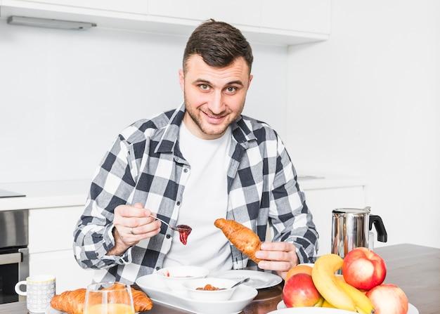 Retrato de hombre joven sonriente que tiene mermelada y croissant en mesa
