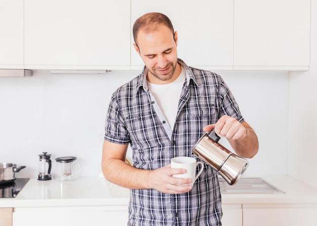 Retrato de un hombre joven sonriente que vierte leche en la taza blanca