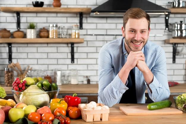 Retrato de un hombre joven sonriente con las verduras coloridas en la tabla en la cocina