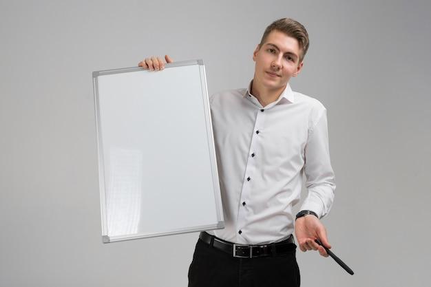 Retrato de hombre joven con tablero magnético limpio y marcador en sus manos aisladas sobre fondo blanco.
