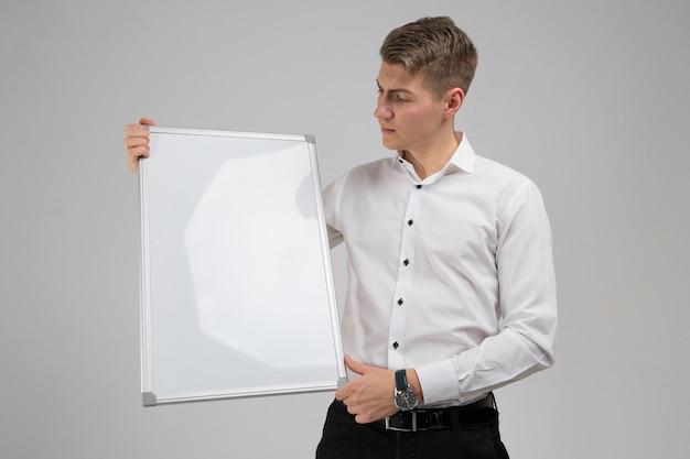 Retrato de hombre joven con tablero magnético limpio en sus manos aisladas en blanco