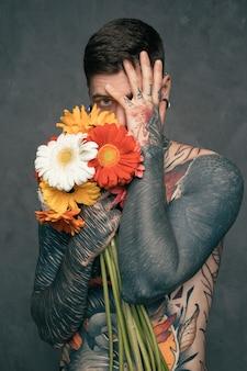 El retrato de un hombre joven tatuado descamisado que sostiene el gerbera florece en la mano