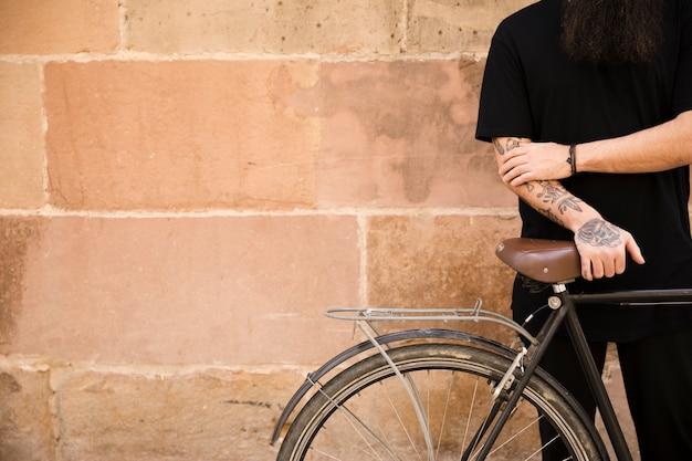Retrato de un hombre joven con tatuaje su mano que se coloca con la bicicleta en la pared