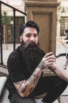 Retrato de hombre joven con tatuaje en su mano sosteniendo la taza de café