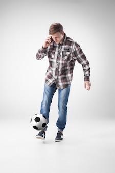 Retrato de hombre joven con teléfono inteligente y pelota de futbol