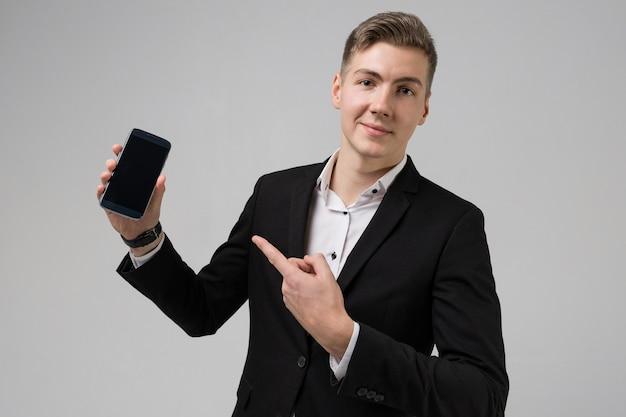 Retrato de hombre joven en traje negro que muestra el dedo en el teléfono móvil con pantalla en blanco aislado en blanco