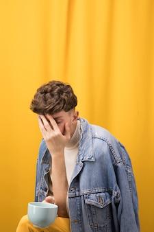 Retrato de hombre joven triste en un escenario amarillo