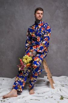 Retrato de un hombre joven triste que se sienta en taburete con el ramo de la flor en su mano