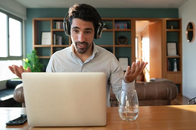 Retrato de hombre joven en una videollamada de trabajo con ordenador portátil desde casa. concepto de oficina en casa. nuevo estilo de vida normal.