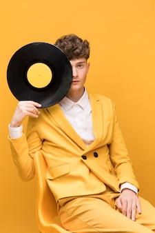 Retrato de hombre joven con un vinilo en un escenario amarillo