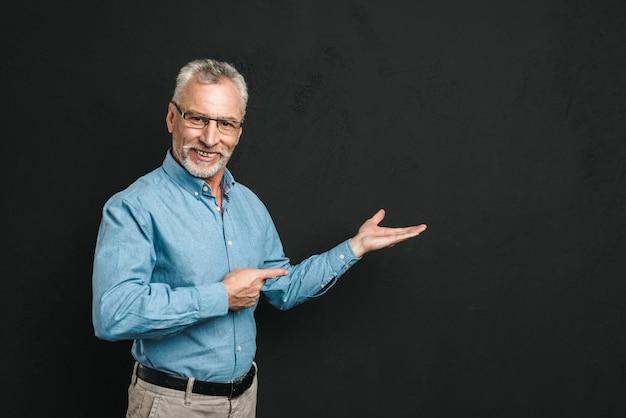 Retrato de hombre jubilado contento 60s con canas y barba en traje sonriendo y demostrando copyspace texto o producto, aislado sobre la pared negra