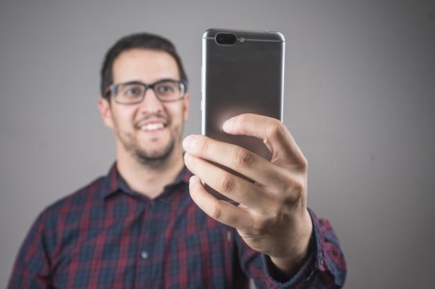 Retrato de hombre jugando con teléfono inteligente o tableta