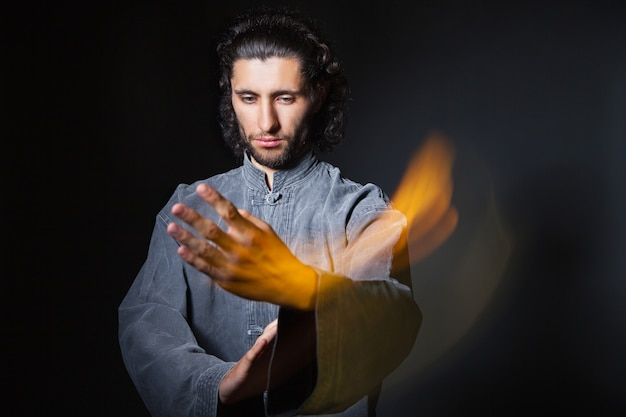 Retrato de hombre en kimono ejercitando artes marciales en fundamento negro con multiexposición