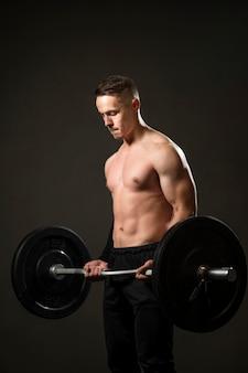 Retrato hombre levantamiento de pesas en el gimnasio