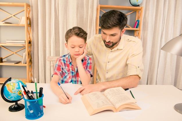 Retrato de hombre leyendo un libro a su pequeño hijo
