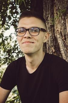 Retrato de hombre lindo joven y sonriente con gafas en el parque
