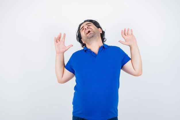Retrato de hombre maduro bostezando y estirando la parte superior del cuerpo en camiseta azul y mirando soñoliento vista frontal