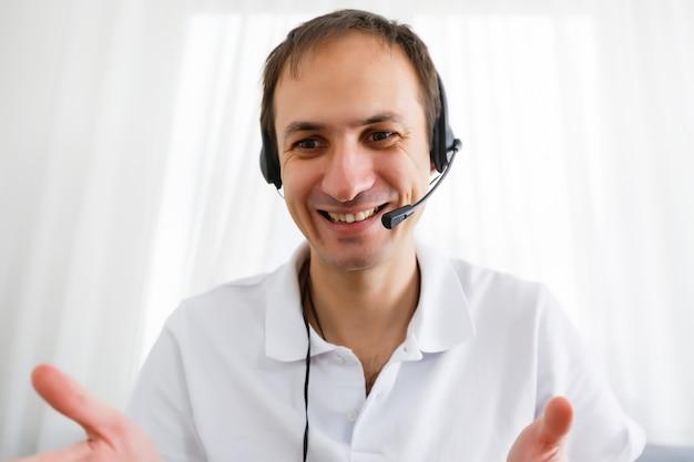 Retrato de hombre maduro feliz haciendo gestos con las manos mientras conversa con una videollamada en la computadora portátil con auriculares