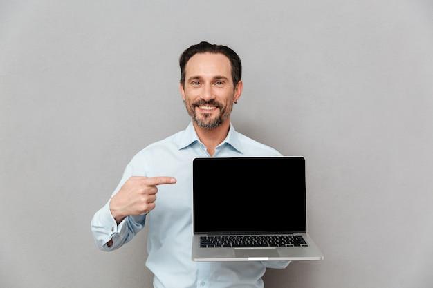 Retrato de un hombre maduro feliz vestido con camisa apuntando