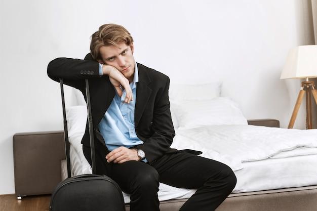 Retrato de hombre maduro hermoso con cabello rubio y barba, acostado en la mano en una maleta, cansado después de un largo vuelo en una reunión de negocios en otro país.