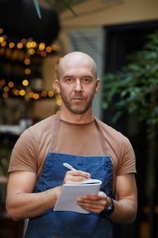 Retrato de hombre maduro en uniforme trabajando como camarero en el restaurante