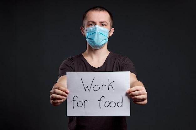 Retrato de un hombre en una máscara médica con un cartel de trabajo para alimentos en una pared oscura, infección por coronavirus