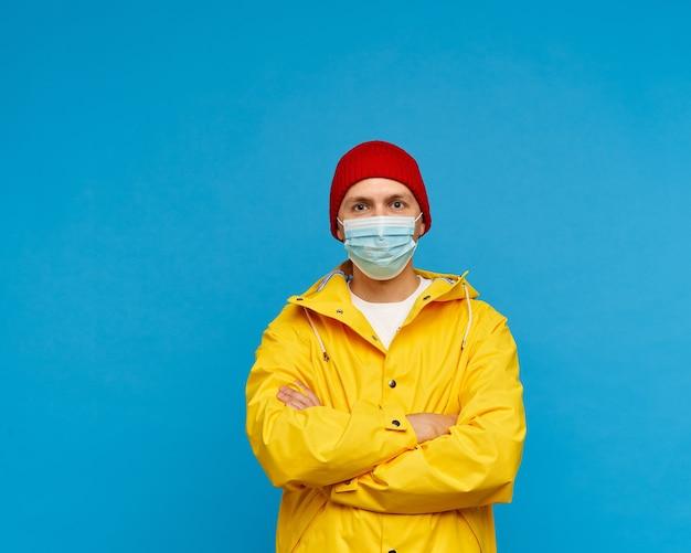 Retrato de hombre con máscara médica protectora se encuentra con los brazos cruzados.