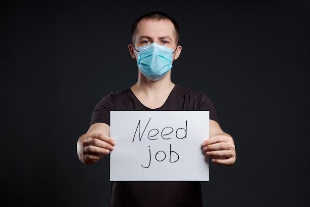 Retrato de un hombre con una máscara médica con un signo de necesidad de trabajo en la oscuridad