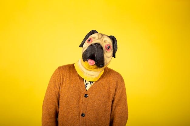 Retrato de un hombre con una máscara de pug en una pared amarilla.