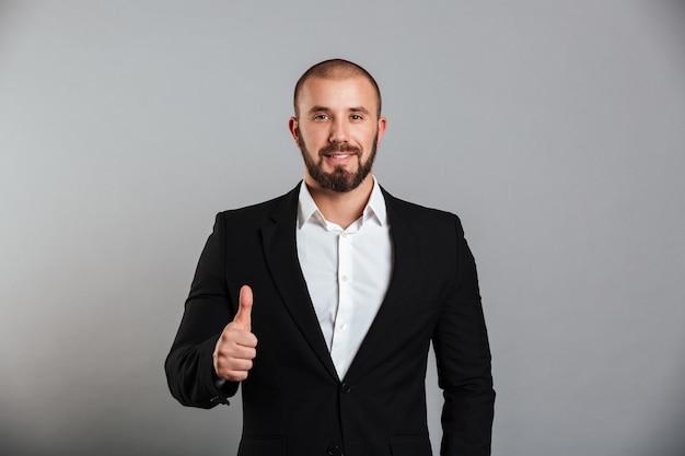 Retrato de hombre masculino complacido en traje de negocios posando en la cámara con el pulgar hacia arriba, aislado sobre la pared gris