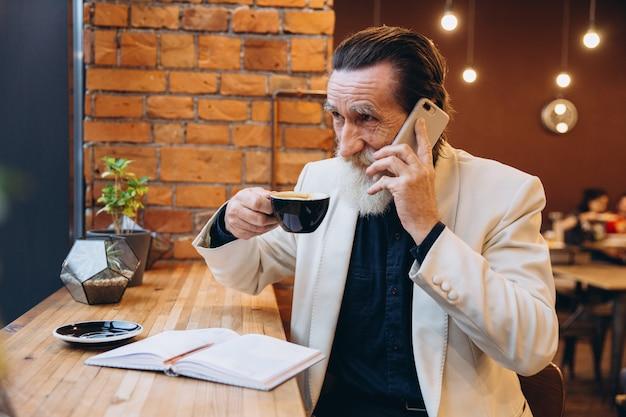 Retrato de un hombre mayor barbudo tomando café y usando el teléfono inteligente en la cafetería. retrato del hombre barbudo gris feliz que se sienta en café.