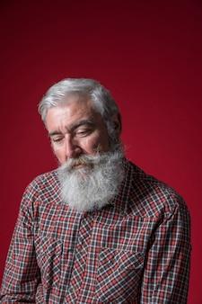 Retrato de un hombre mayor deprimido contra fondo rojo