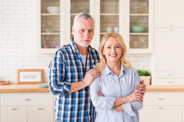 Retrato del hombre mayor feliz que se coloca detrás de la mujer en cocina