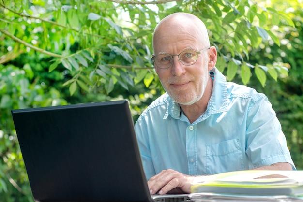 Retrato de hombre mayor con gafas, al aire libre