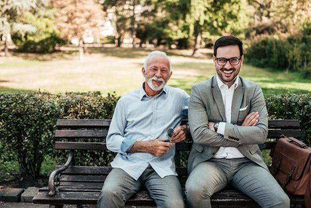 Retrato del hombre mayor y joven elegante que se sienta en un banco en el parque.